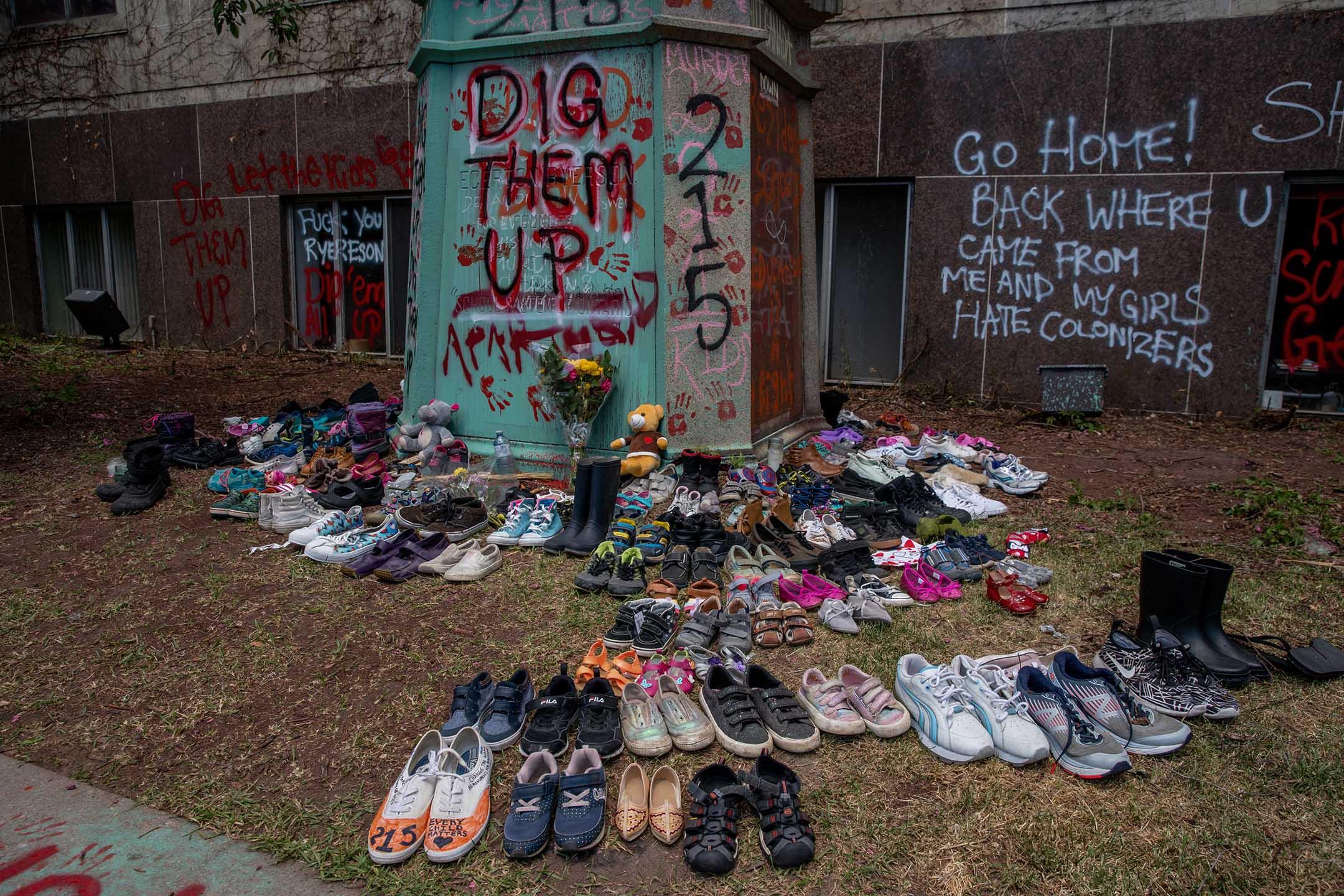 2021年6月1日加拿大多倫多瑞爾森大學,加拿大原住民寄宿學校創建者雕像旁放置了 215 只鞋子,紀念不列顛哥倫比亞省坎盧普斯市的寄宿學校内一個坑中發現的 215 具學生屍體。 攝:Shawn Goldberg/LightRocket via Getty Images