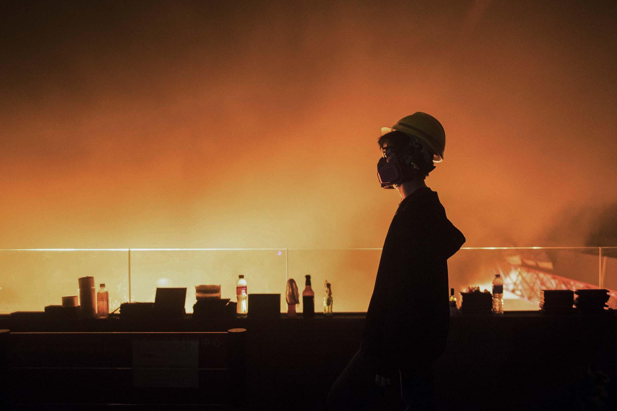 2019年11月18日香港理工大學,一名示威者在燃燒的校園內。 攝:陳焯煇/端傳媒