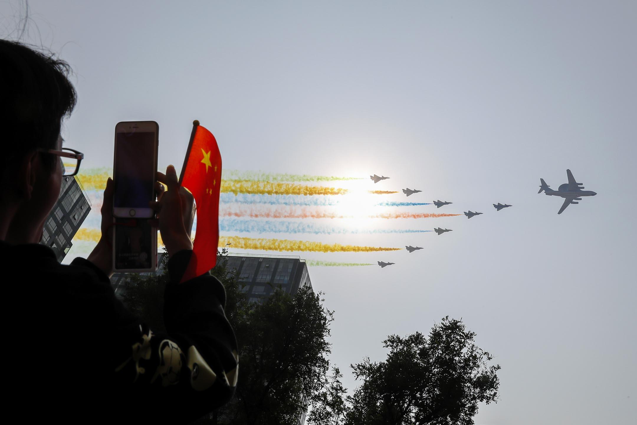 2019年10月1日,北京舉行的慶祝中國共產黨成立 70 週年的閱兵式上,一名男子用他的智能手機拍攝飛行中的中國軍機與彩色煙霧。