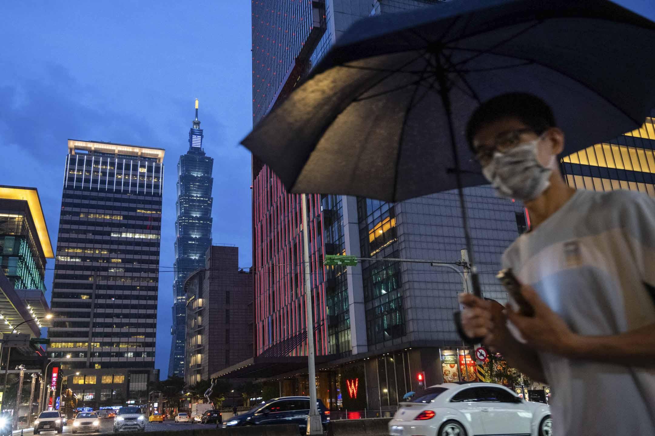 2021年5月21日,一名戴著口罩的行人時舉著雨傘經過台北 101 大樓前。 攝:Billy H.C. Kwok/Bloomberg via Getty Images