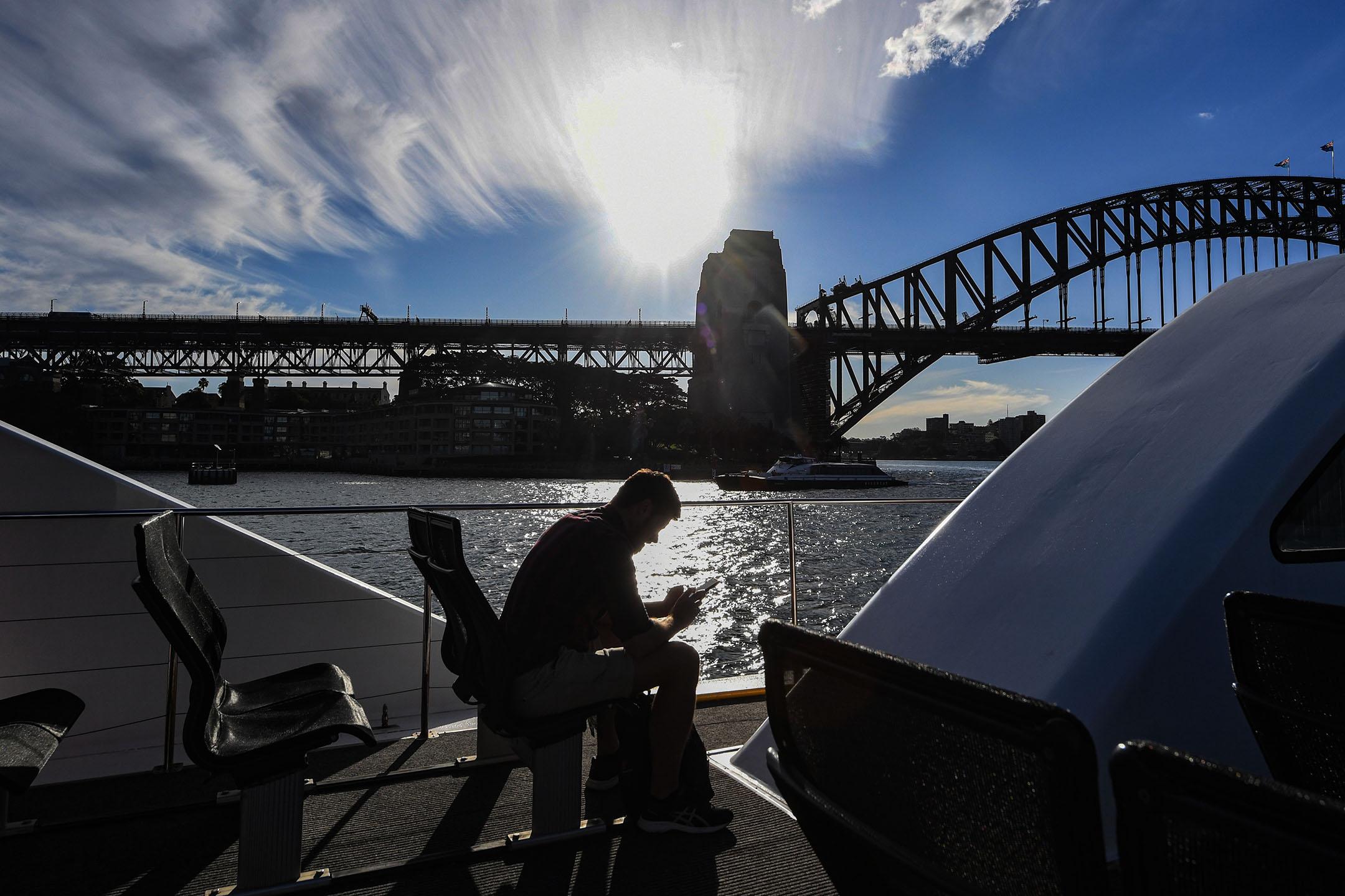 2020年5月12日澳大利亞悉尼,一名男子乘坐悉尼渡輪經過海港大橋時看手機。 攝:James D. Morgan/Getty Images