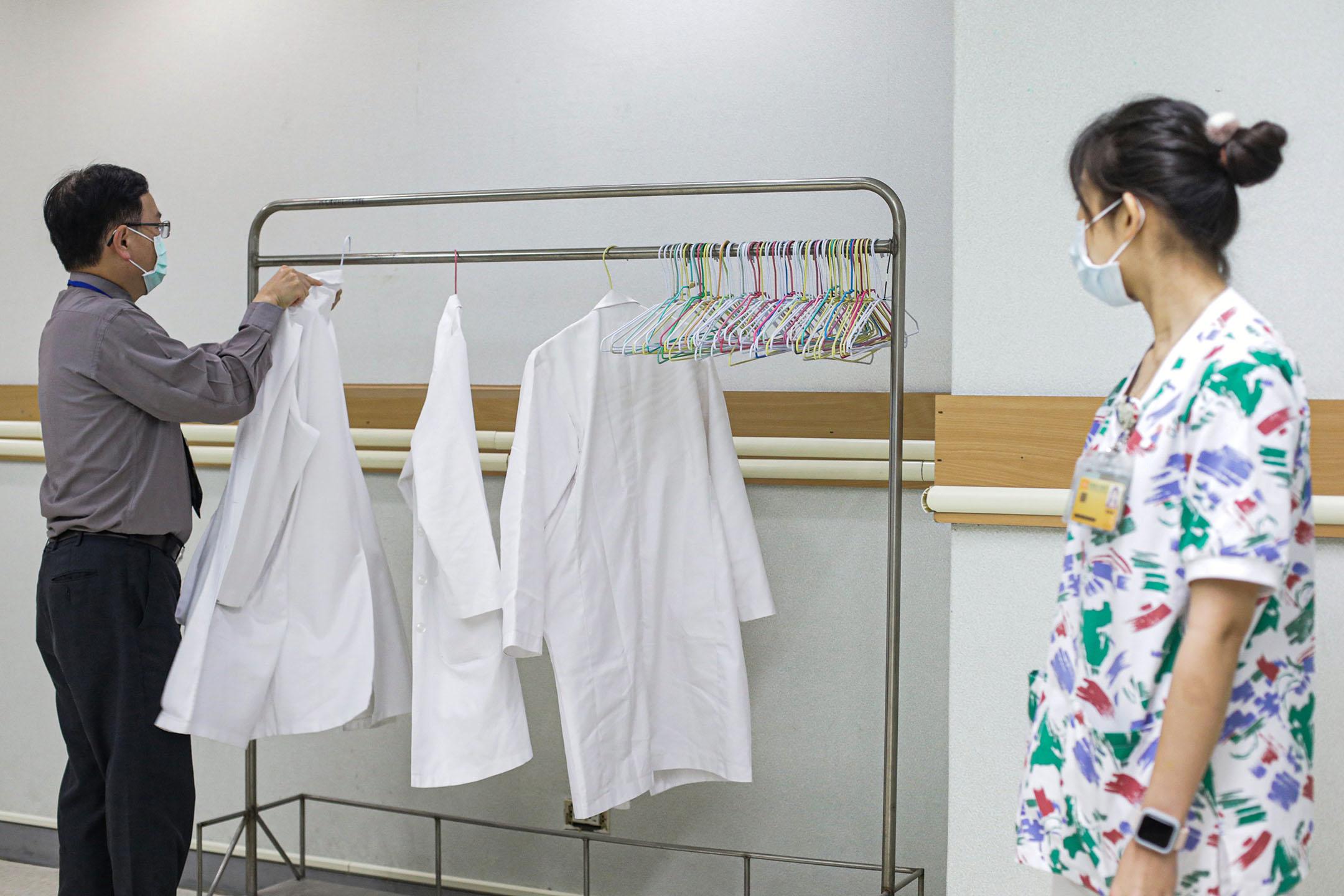 2021年3月22日台灣台北,一名醫生在接種阿斯利康疫苗前將一件白色外套掛在架子上。 攝:I-Hwa Cheng/Bloomberg via Getty Images