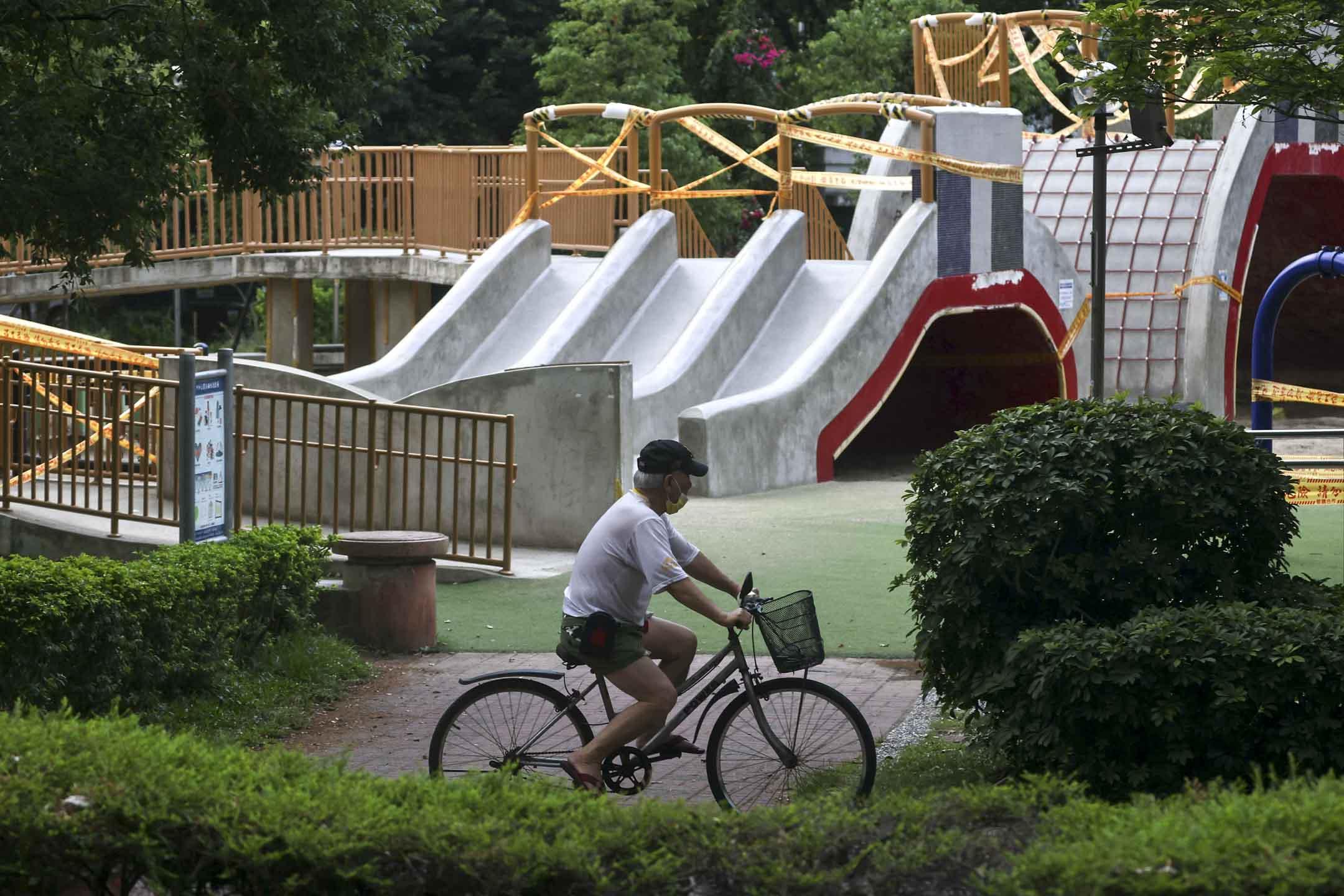 2021年5月21日,台北新冠病毒感染率上升後,男士騎單車經一個關閉中的公園。 攝:Ann Wang/Reuters/達志影像
