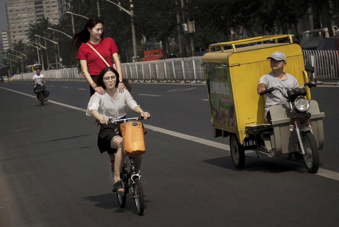 北京兩位女士一起騎著單車。 攝:Kevin Frayer/Getty Images