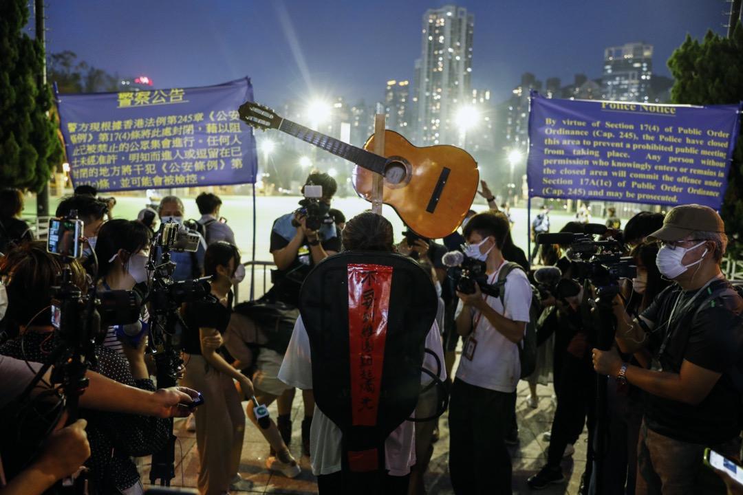 2021年6月4日,藝術家三木在維園閘前舉起吉他,背上貼上「不要到維園點起燭光」字句。
