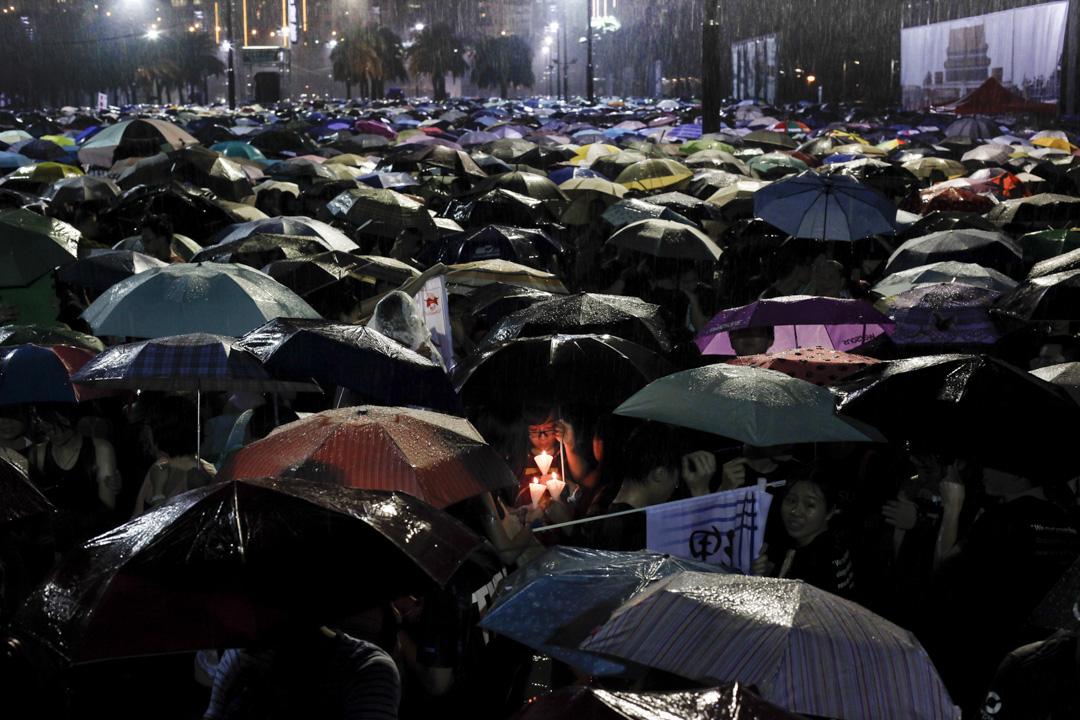 2013年6月4日,維園燭光晚會照常在8時開始,但開始前15分鐘前突然下起暴雨,現場市民舉起雨傘並保護著燭光,最後晚會在進行了大約半小時後宣布提前結束。支聯會宣布當晚共有15萬人出席。 攝:李澤彤/明報