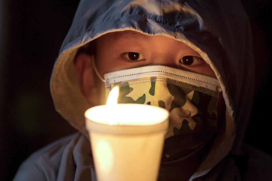 2021年6月4日,美國加州洛杉磯,一名男孩手持蠟燭,參加在中國領事館外舉行的六四悼念集會。
