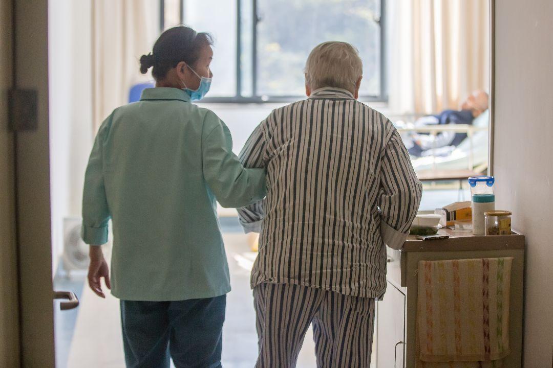 2020年11月12日,中國杭州市同德醫院,一名醫護人員陪一名阿茲海默症患者散步。 攝:Chen Zhongqiu/Getty Images
