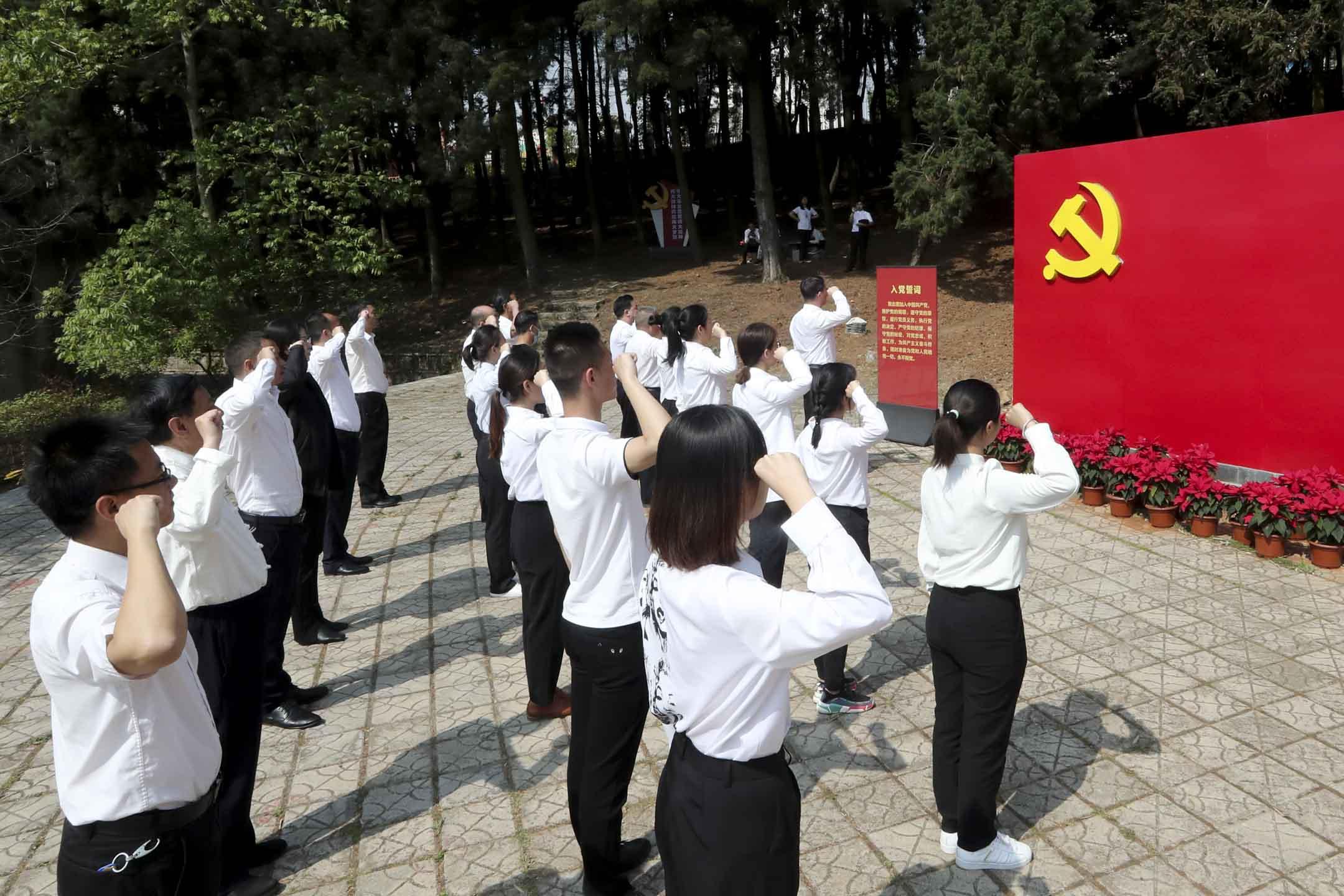 2021年3月28日,雲南,共產黨黨員參觀中共雲南省第一次代表大會遺址紀念碑,期間在旗牌前宣誓。 攝:Yang Zheng/VCG via Getty Images