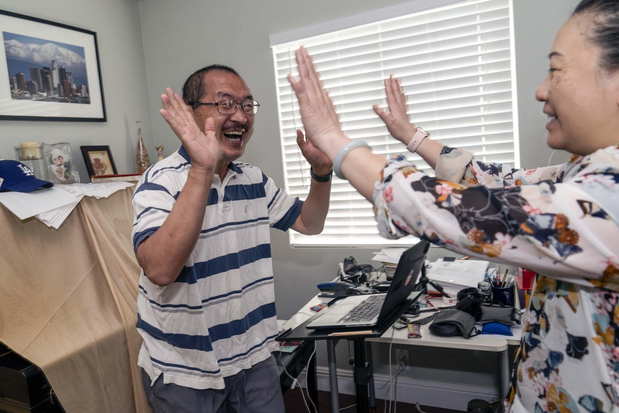 2021年6月11日,移居美國多年的美聯社港人攝影師趙漢榮 Ringo Chiu 得知自己獲普立茲獎後與太太 Suki 慶祝。 攝:Damian Dovarganes/AP/達志影像