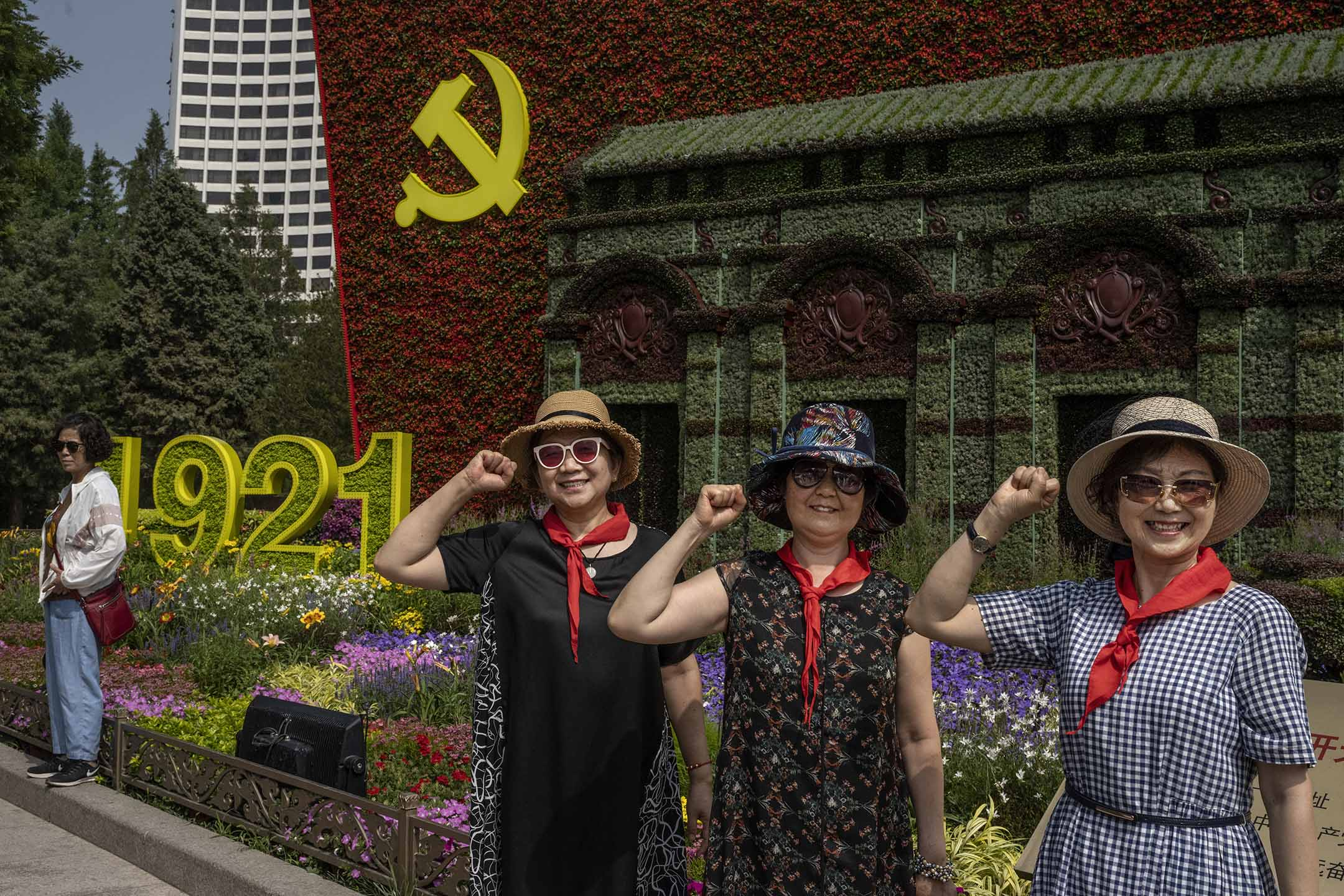 2021年6月27日中國北京,街道上設置的花展上,婦女們在中國共產黨的大型標誌前拍照。