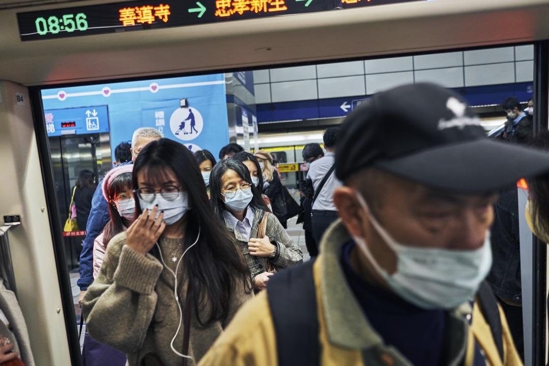 台北捷運站,乘客戴口罩進入車廂。 攝:An Rong Xu/Getty Images
