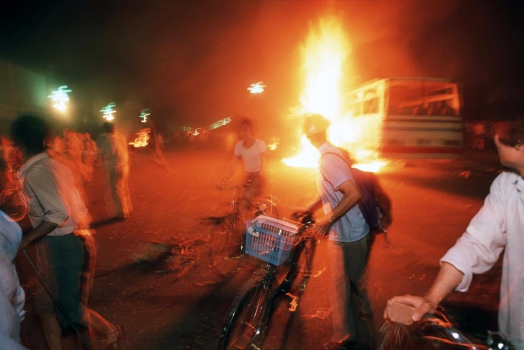 1989年6月4日,北京,解放軍向天安門廣場方向開槍,廣場上的人民逃到長安大街,期間經過被焚燒的車輛。