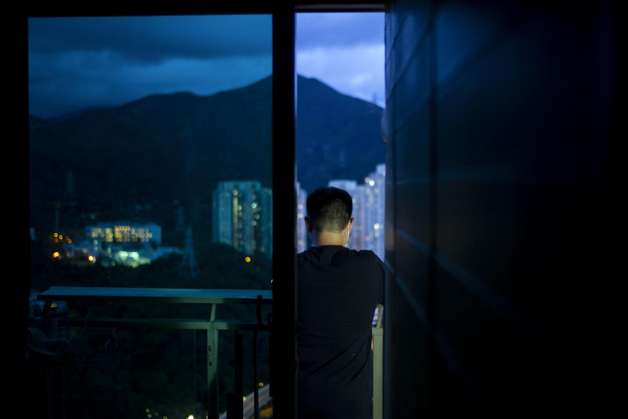 40多歲的林天昇(化名)在他的豪宅劏房露台上遙看景色。 攝:林振東/端傳媒