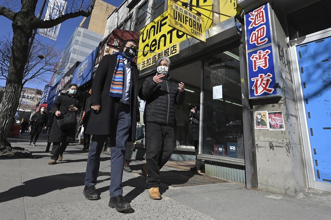 2021年2月25日紐約皇后區,紐約市市長民主黨候選人楊安澤(左)和當地商人走在唐人街。