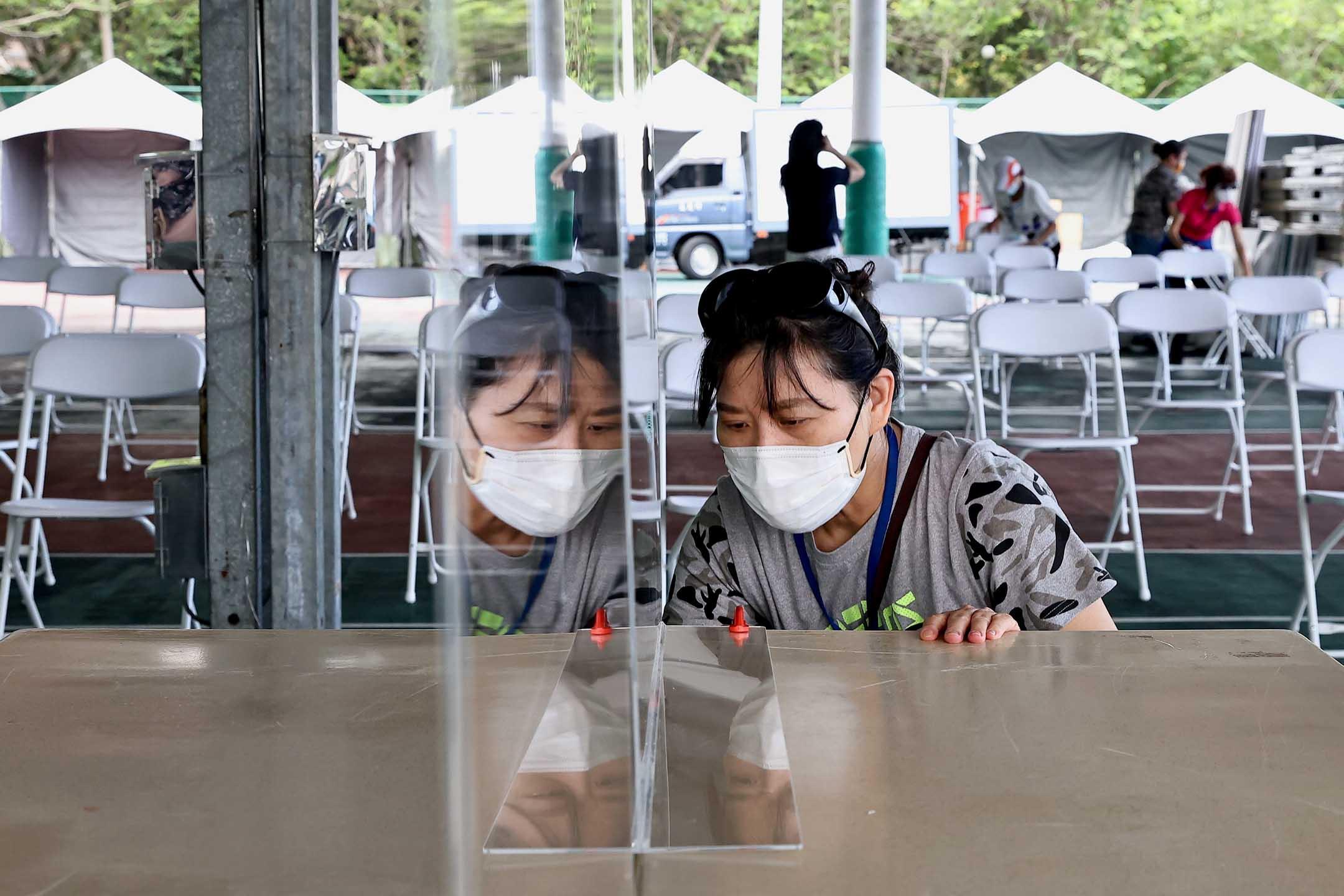 2021年6月8日台灣新竹,一名戴著口罩的婦女在網球場設置了一塊隔板,該網球場被改造成臨時疫苗接種點。 攝:Ann Wang/Reuters/達志影像