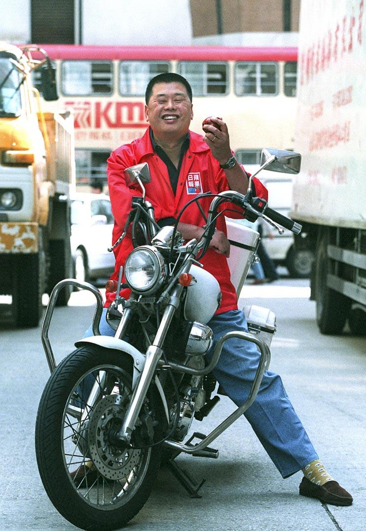 1995年11月3日,《蘋果日報》創辦人黎智英在長沙灣道的辦公室外騎著突發記者常用的採訪電單車。
