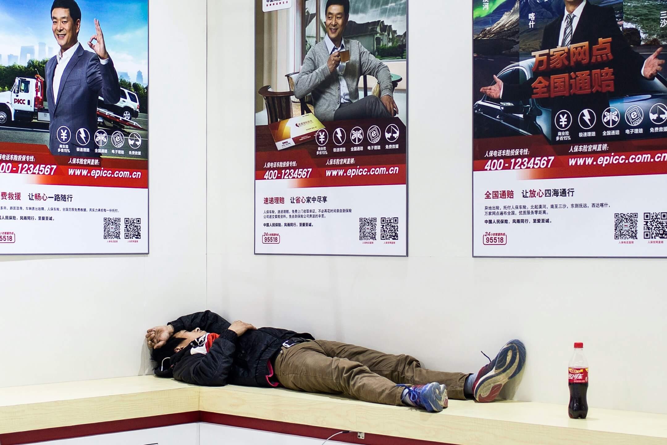 廣州國際汽車展覽會,一名布展的工人在展示板前躺下休息。