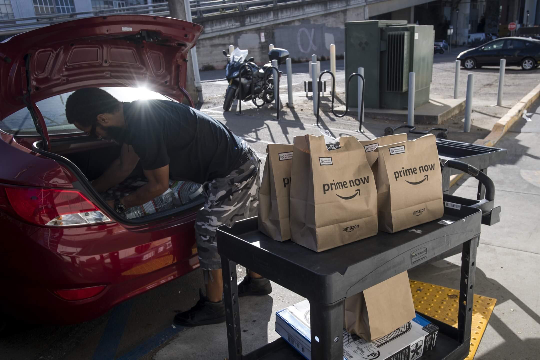 一名亞馬遜Flex的合約司機把貨物搬到車上預備配送。 攝:David Paul Morris/Bloomberg via Getty Images