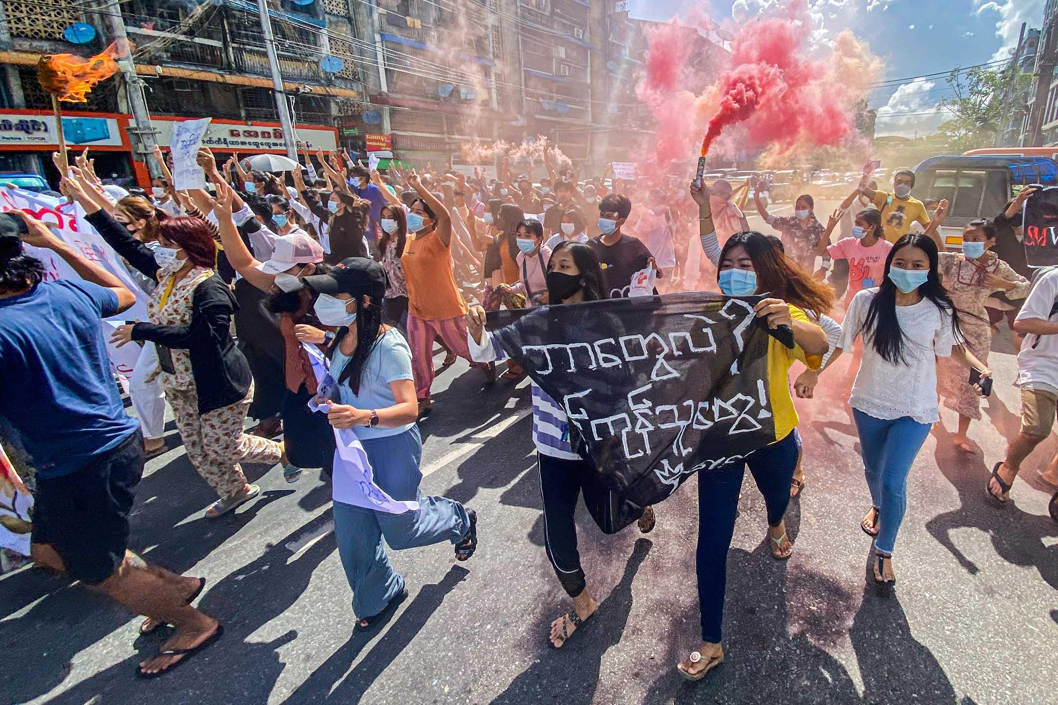 2021年7月14日緬甸仰光,反政變示威遊行期間,婦女手持橫幅和緊急信號棒奔跑。