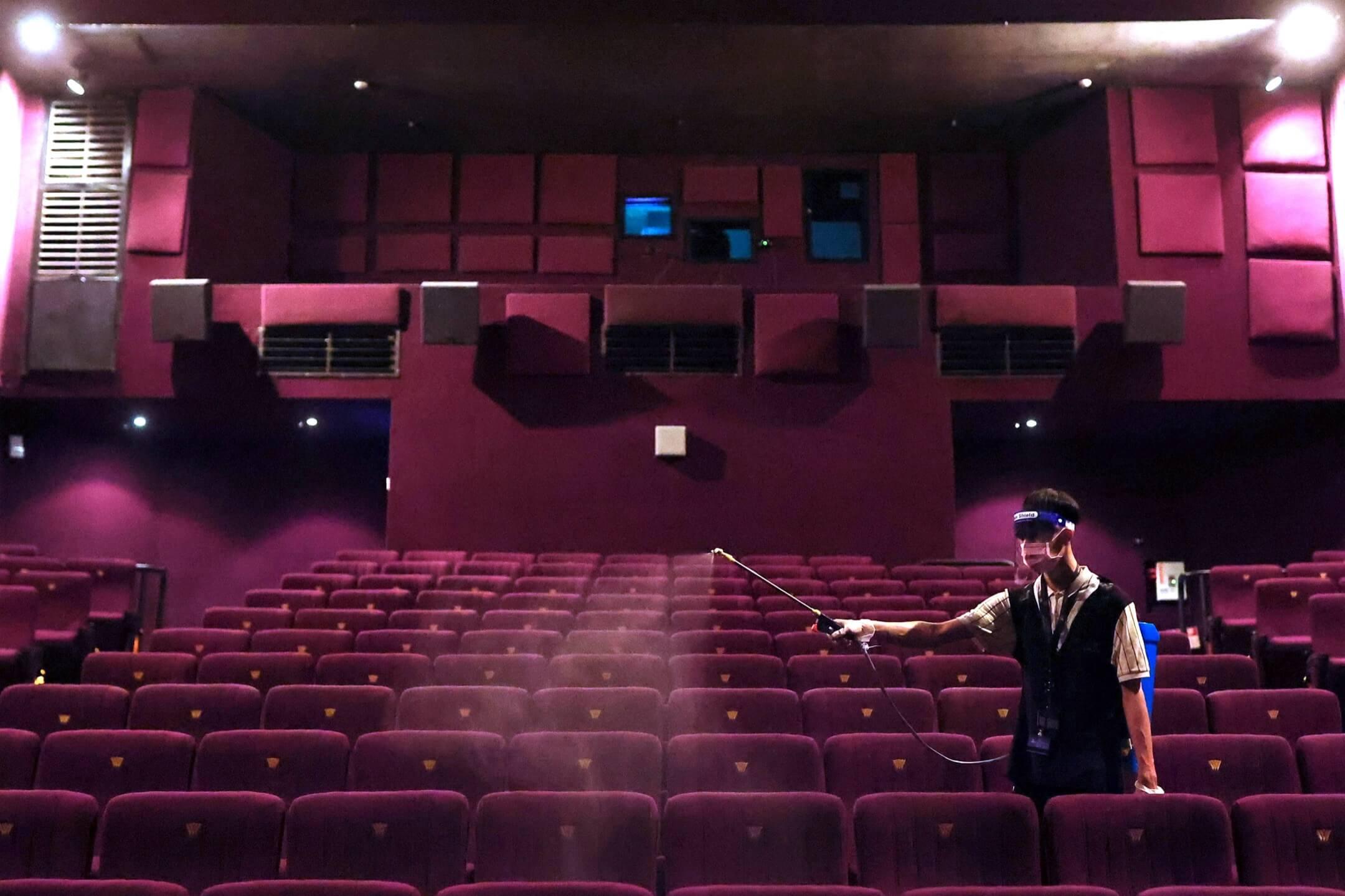 2021年7月13日,台北市一家戲院的工作人員為院內的椅子進行消毒。台灣中央流行疫情指揮中心日前宣布放寬防疫措施,其中包括重開戲院。 攝:Ann Wang/Reuters/達志影像