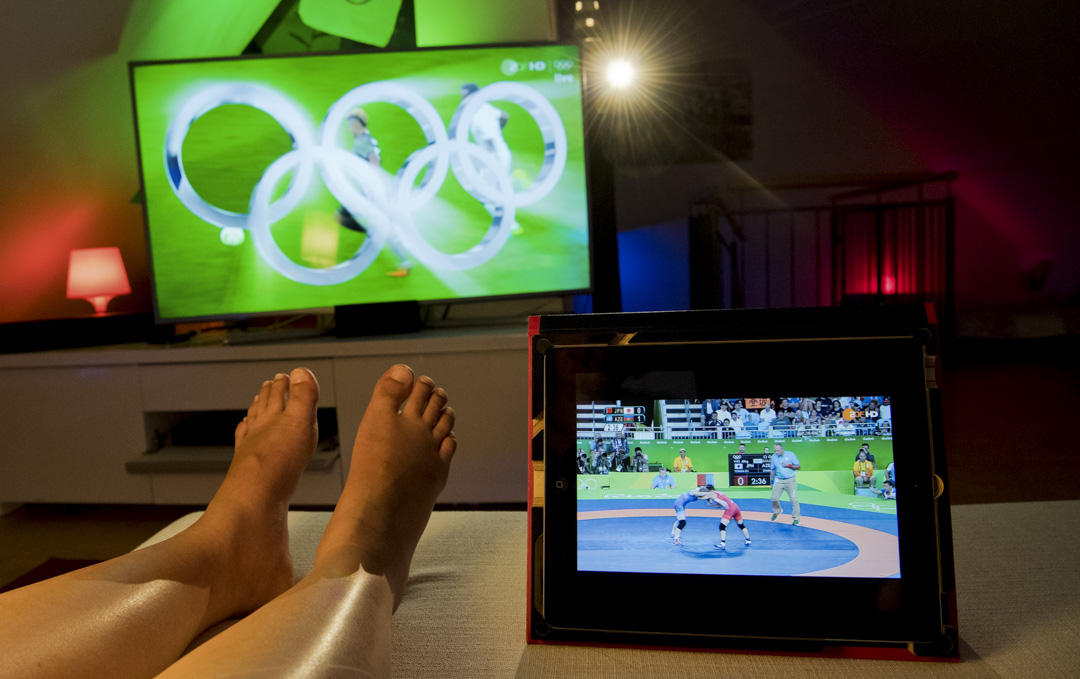 2016年8月17日,德國漢諾威的一個客廳裡,觀眾通過電視和平板電腦上觀看奧運摔跤比賽現場直播。
