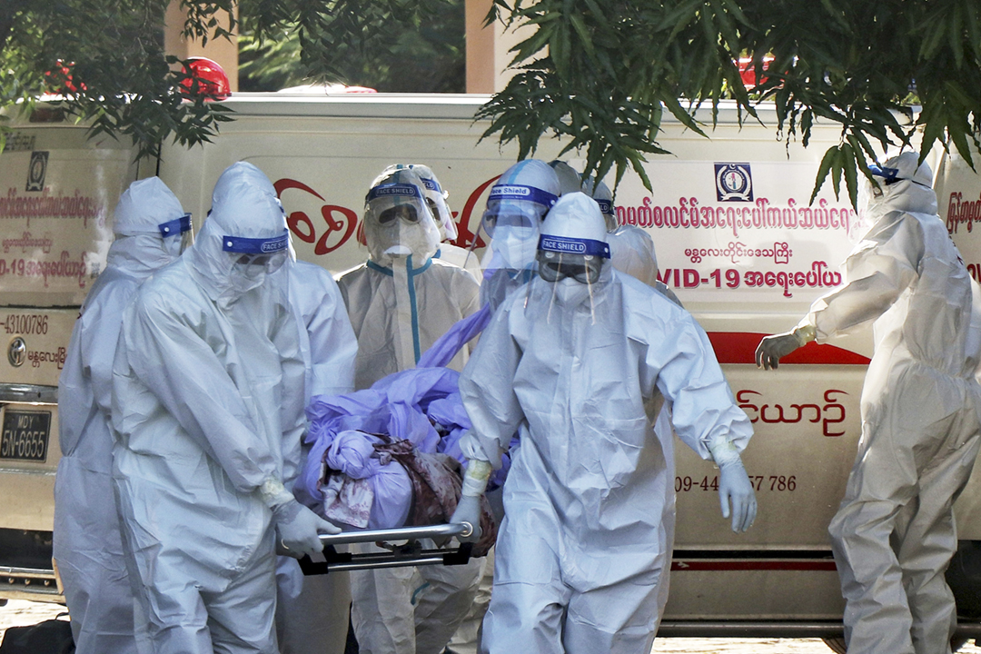 2021年7月14日在緬甸曼德勒,數名志願醫護人員正處理「2019 冠狀病毒」染疫死者的屍體。 攝:Stringer / Reuters