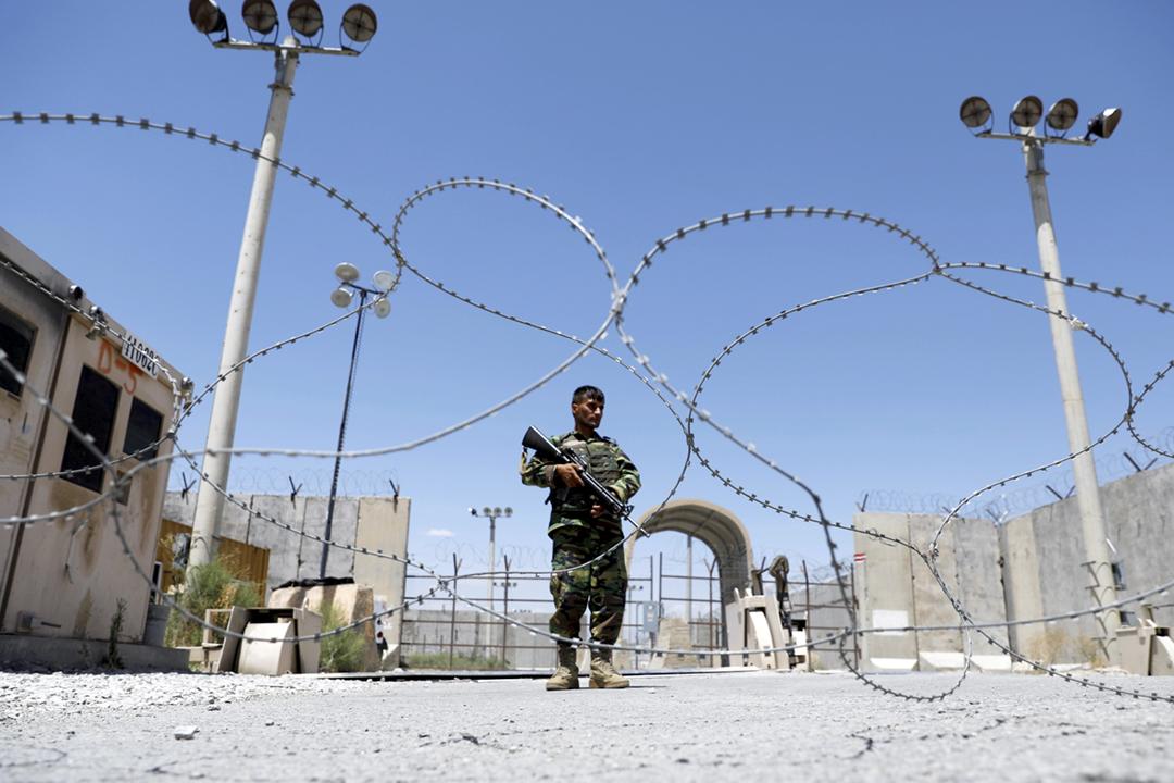 2021年7月2日,美軍完全撤出在阿富汗境內規模最大的巴格拉姆空軍基地,一名阿富汗安全部隊士兵在基地閘口站崗。 攝:Mohammad Ismail / Reuters