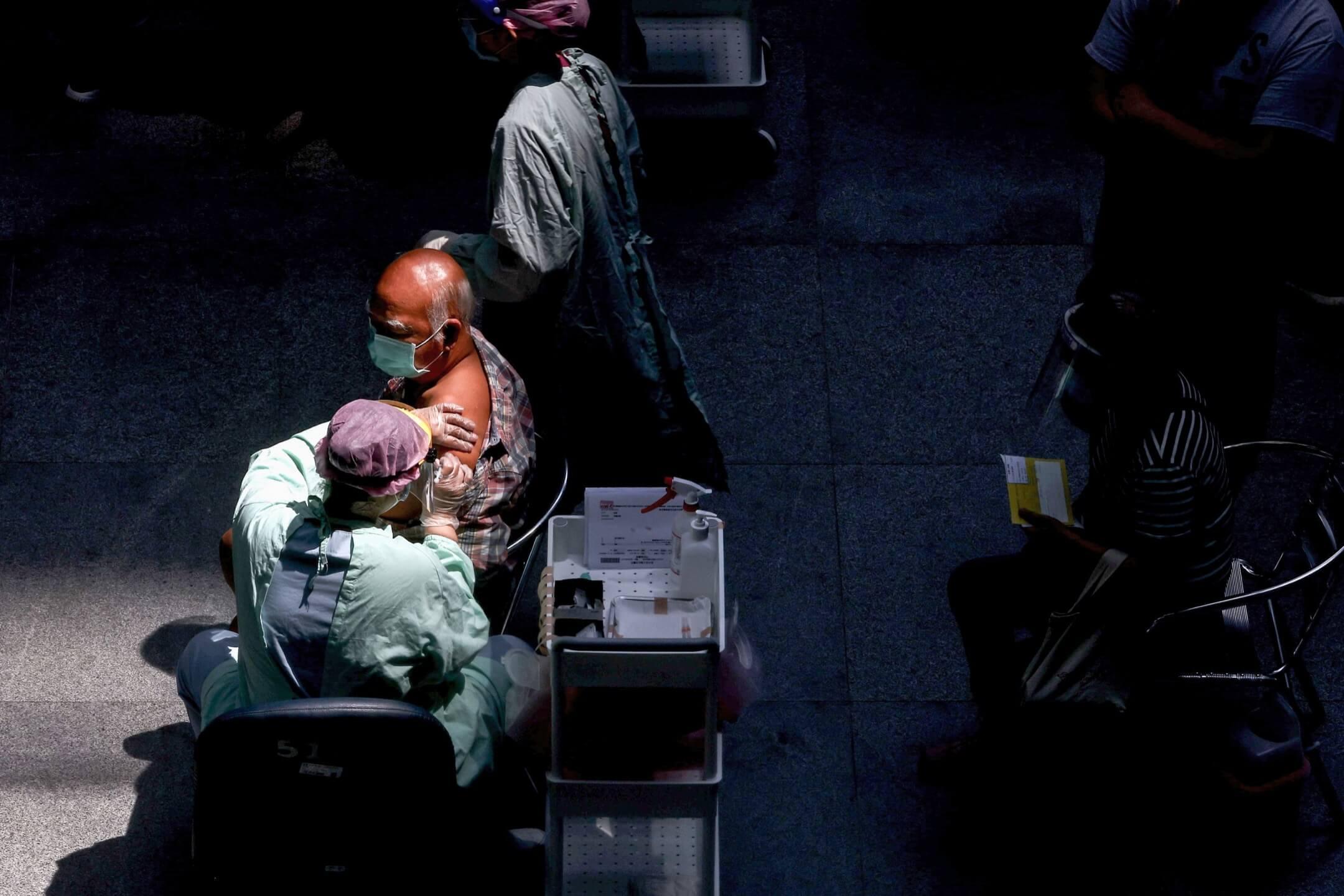2021年7月3日,台灣台北市國立臺灣科學教育館,一位醫護人員為一名市民接種莫德納(Moderna)疫苗。 攝:Ann Wang/Reuters/達志影像