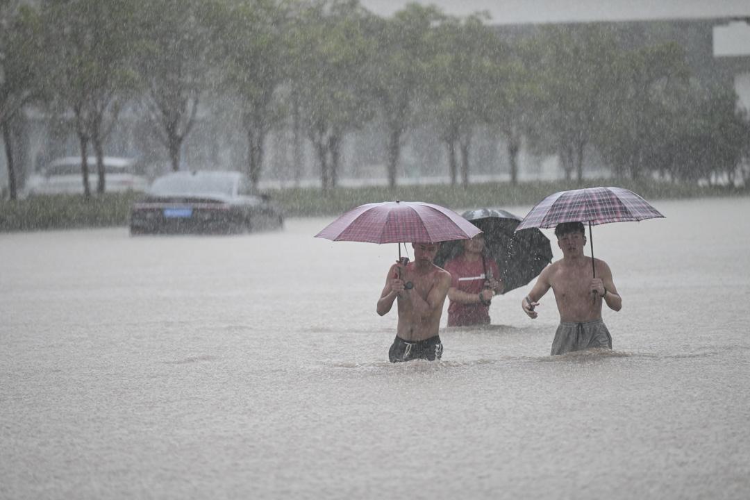 2021年7月20日,河南省鄭州市,人們在鄭州火車站附近的洪水中行走。