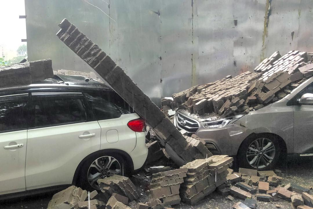 2021年7月20日,河南省鄭州市傾盆大雨後,倒塌的牆壁損壞了一架汽車。