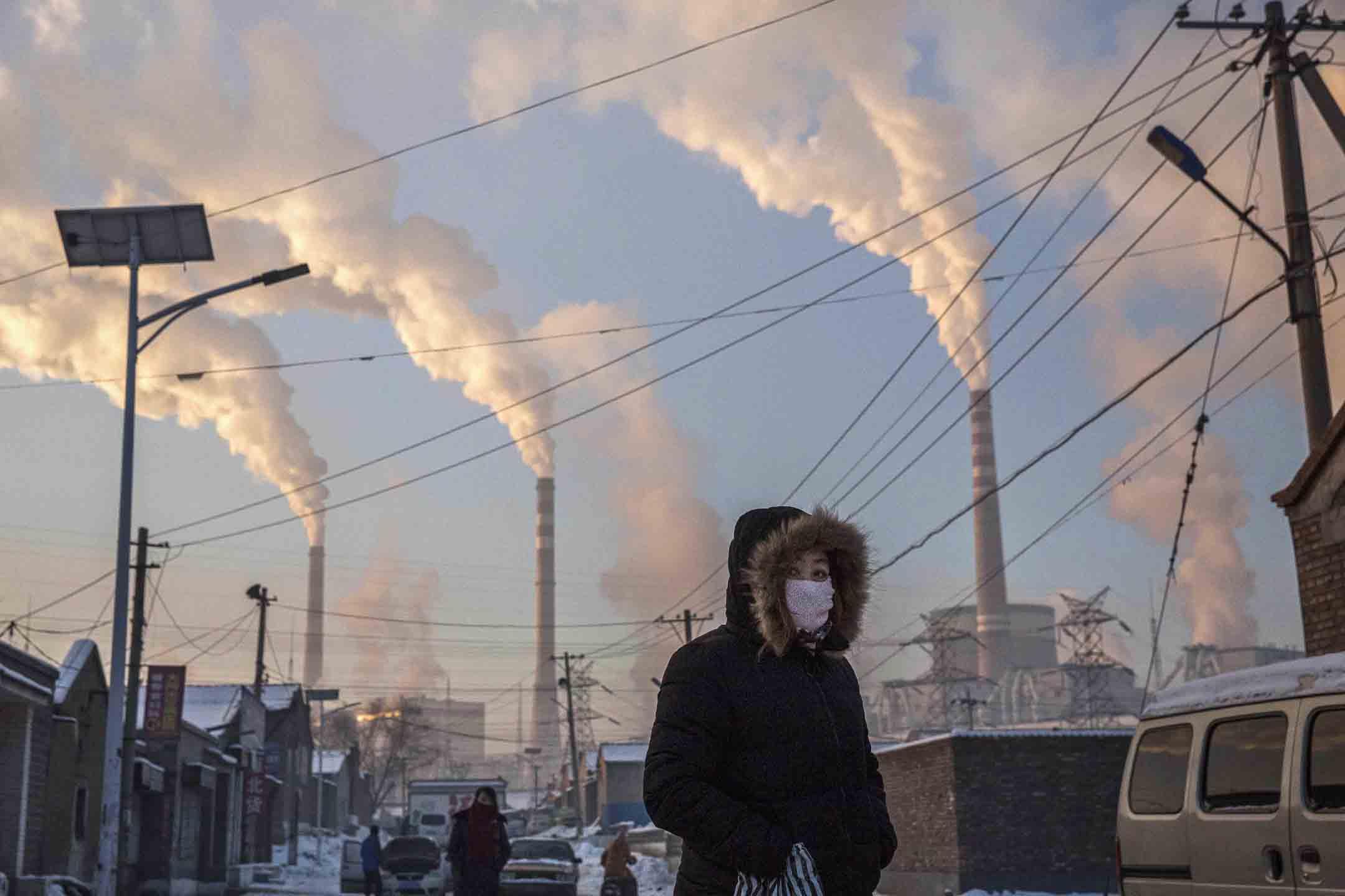 2015年11月26日中國山西,一名戴著口罩的中國婦女走在燃煤電廠附近的街道。