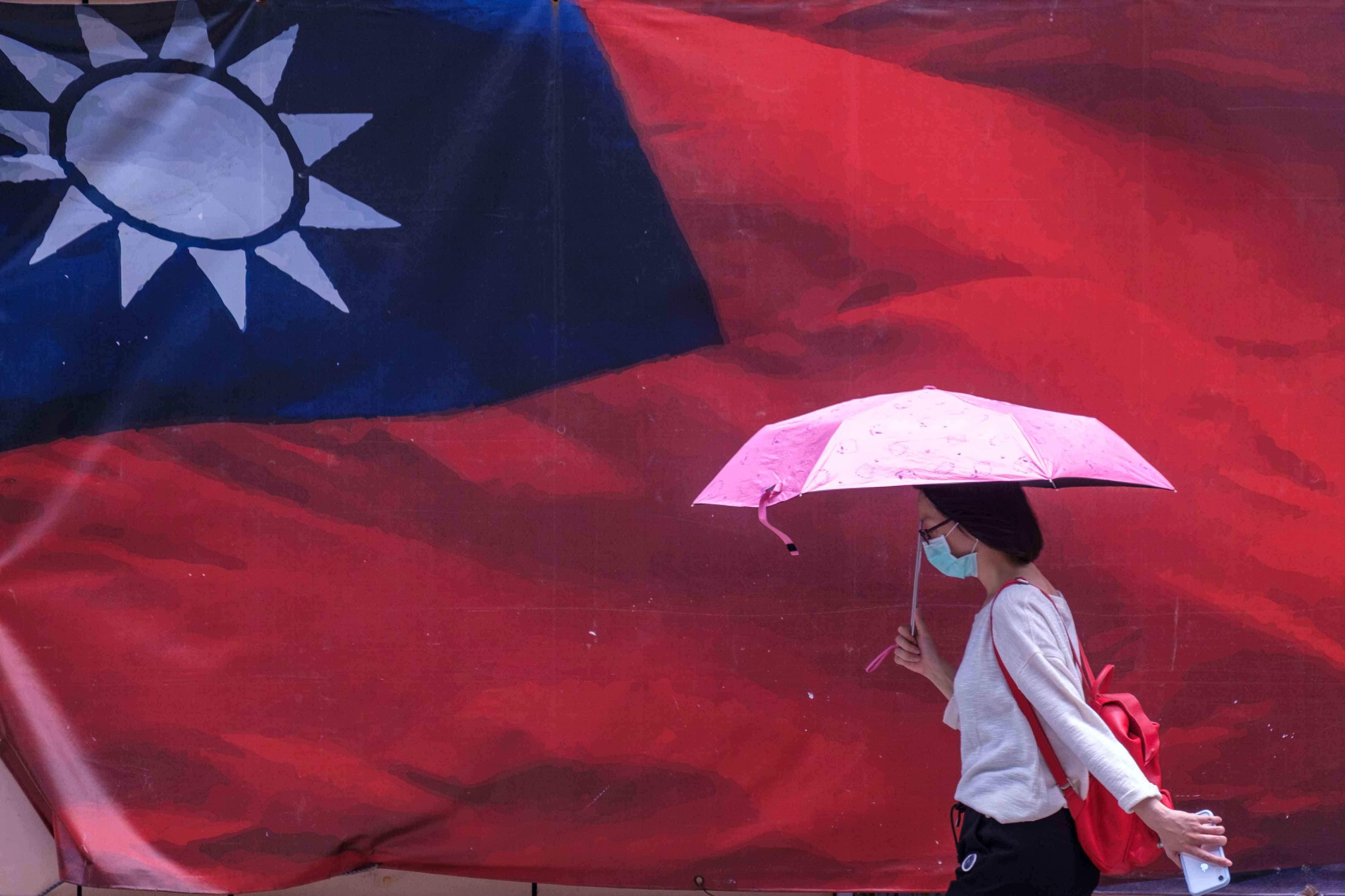 2021年7月19日台灣台北,一名戴著口罩拿著雨傘的婦女走過台灣國旗。