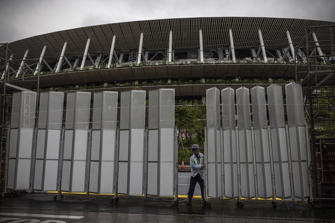 2021年7月8日,東京,一名保安關閉奧運體育場的大門。