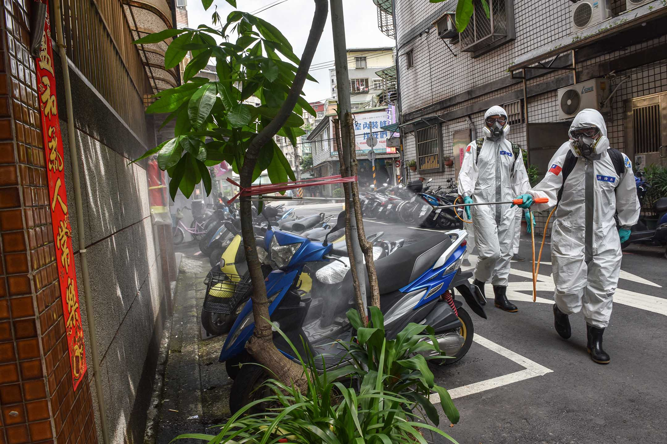 2021年5月26日台灣台北,身穿防護服的軍人在街道上消毒。