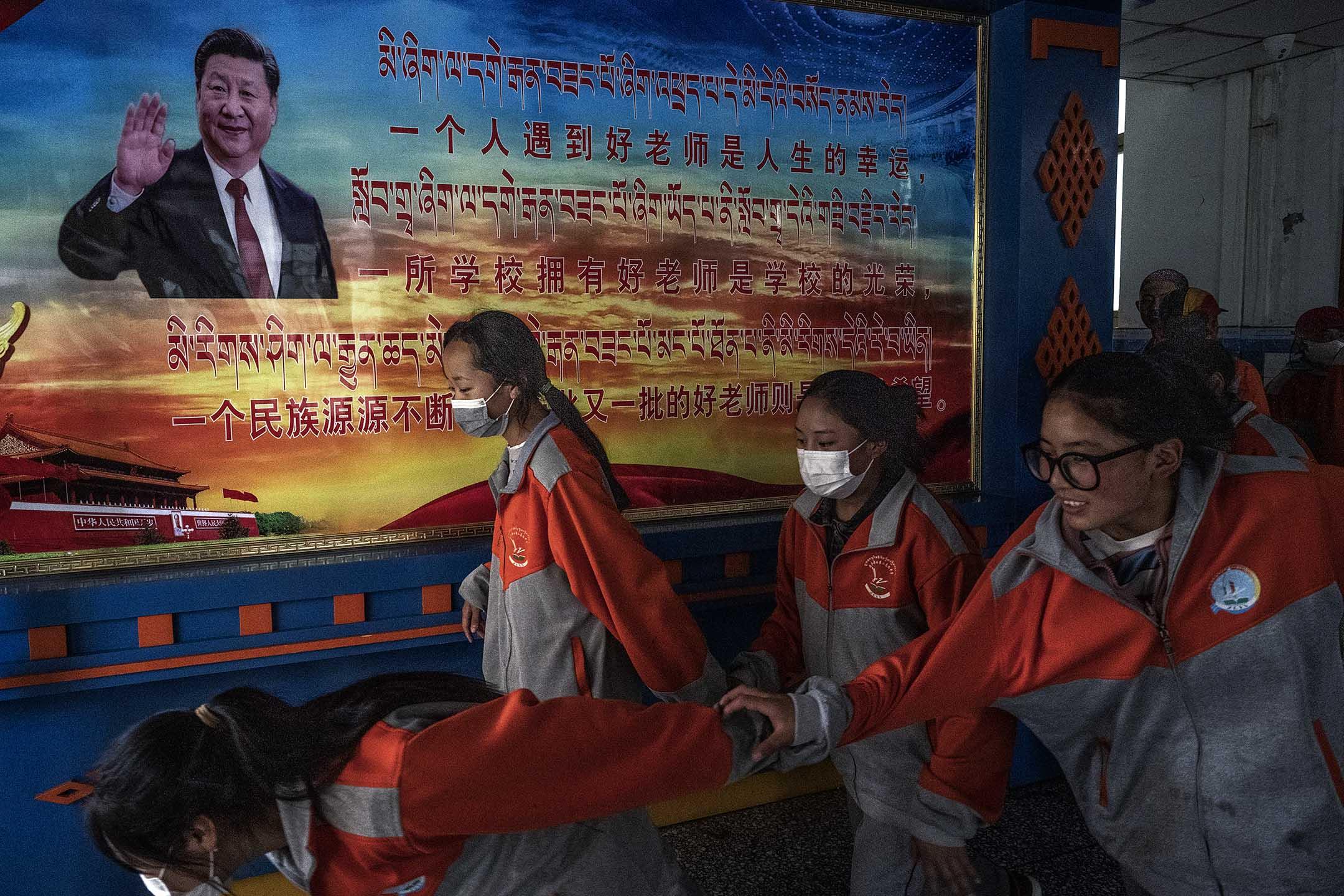 2021年6月1日中國拉薩,西藏中學學生下課時經過一張習近平主席的海報。 攝:Kevin Frayer/Getty Images