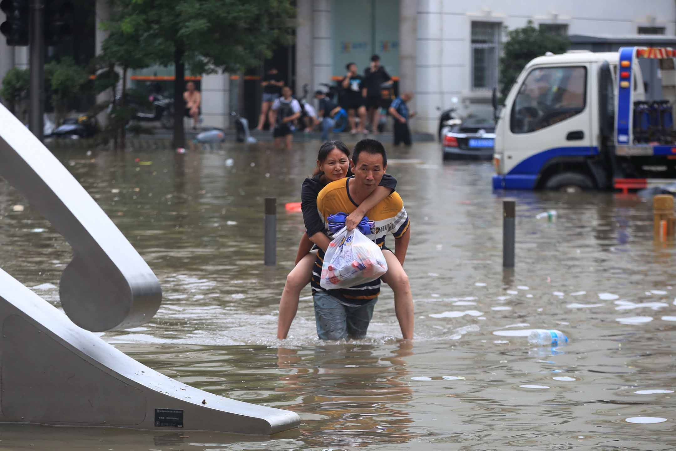 2021年7月20日中國鄭州,傾盆大雨後,一名男子在被洪水淹沒的道路上背著一名婦女。