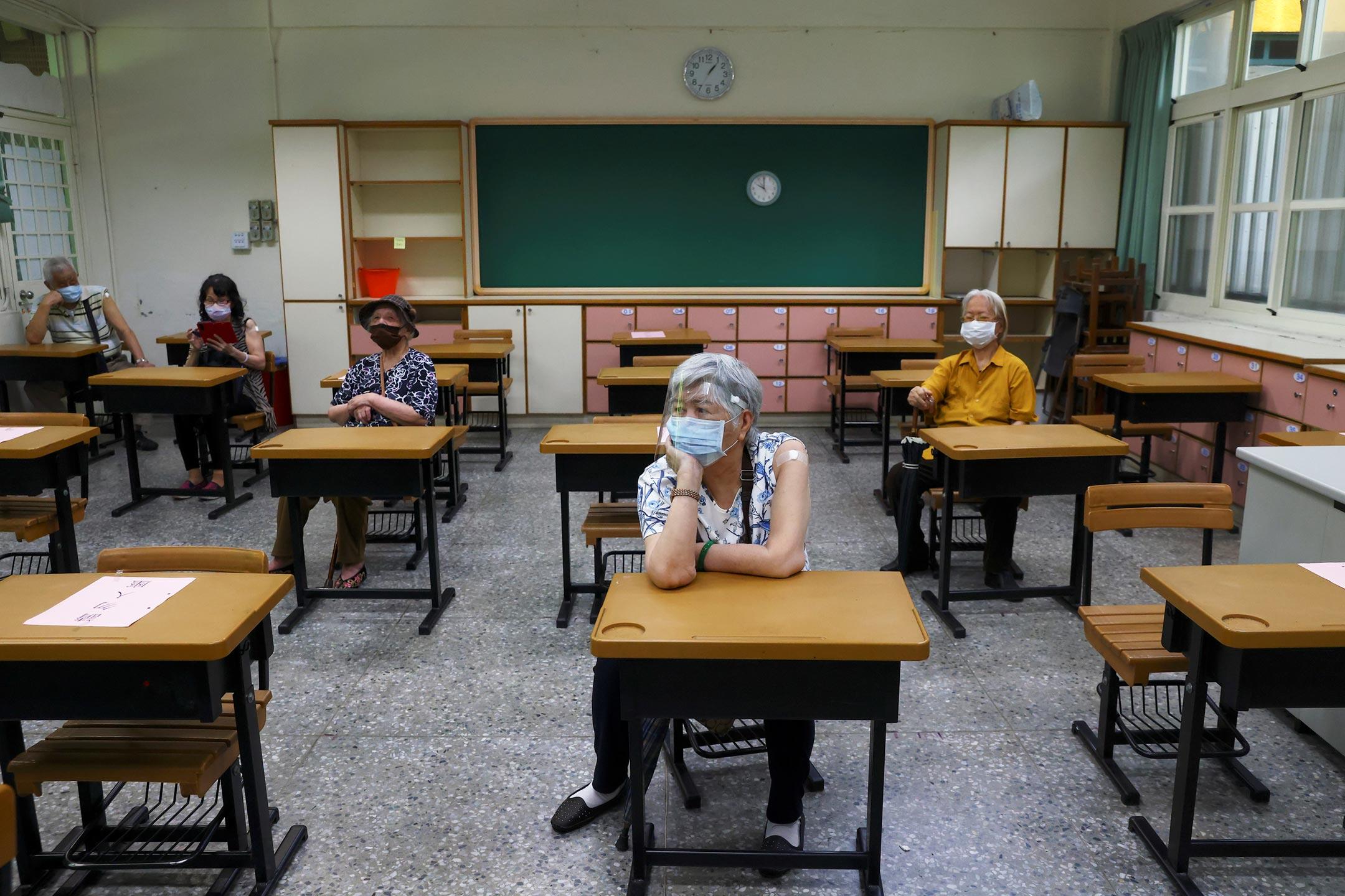 2021年6月15日,台北一所學校為 85 歲以上老年人接種疫苗,接種後的人士在觀察區等待。 攝:Ann Wang/Reuters/達志影像