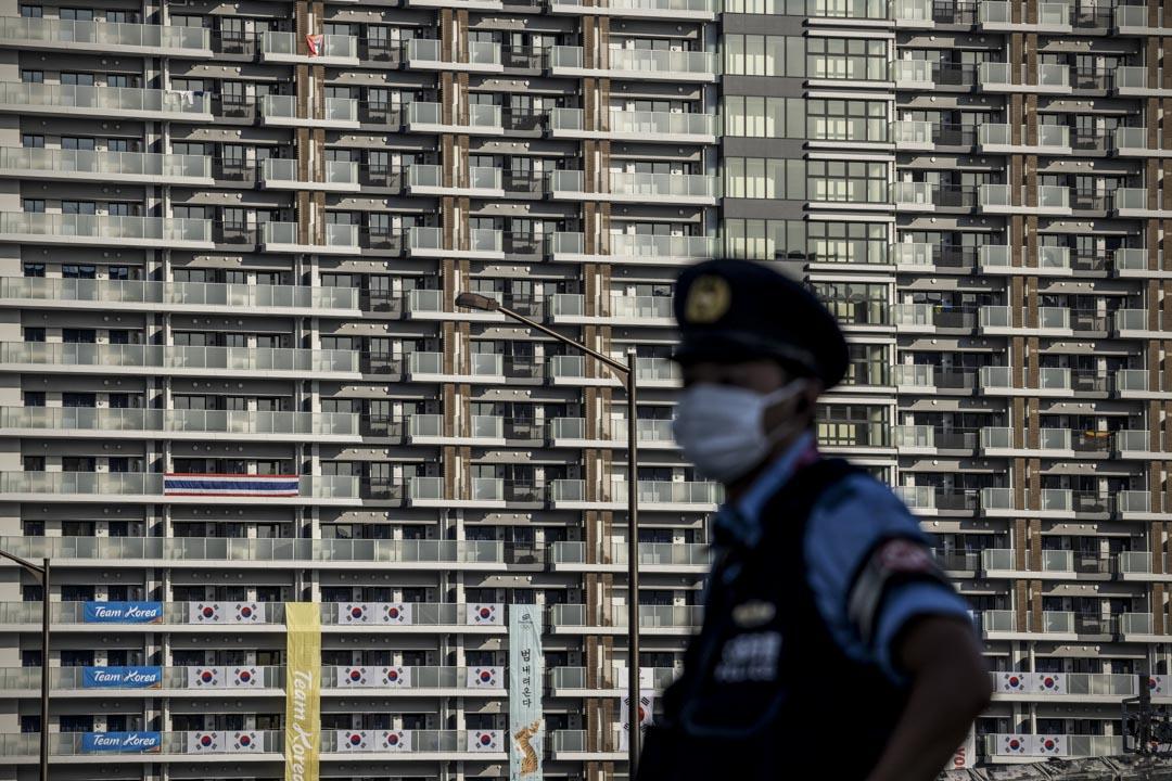 2021年7月19日,東京一名警察在東京奧運會運動員村的住宿樓旁站崗。