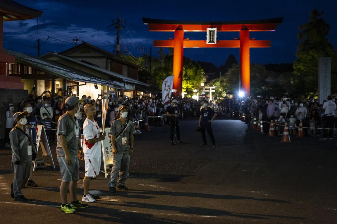 2021年6月25日,日本富士宮舉行的東京奧運會火炬傳遞期間,一名火炬手在接力點等待。