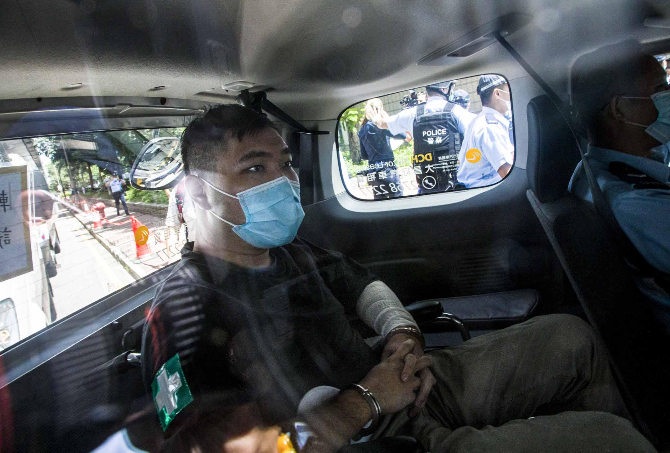 2020年7月6日,唐英傑被控駕駛插上「光復香港 時代革命」旗幟的電單車撞向警察,被指違反《國安法》下「煽動他人分裂國家罪」和「恐怖活動罪」等,由警車押送至法院提堂。 圖:Getty Images