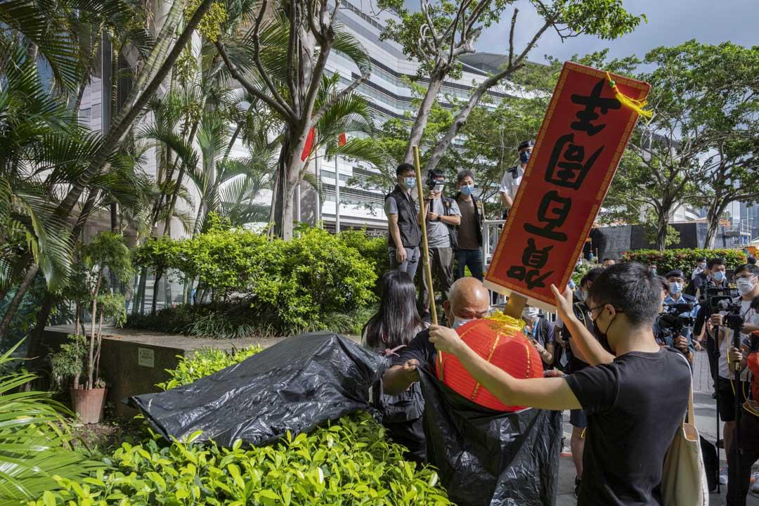 2021年7月1日香港灣仔,社民連的成員拿著寫上「賀百周年」紅燈籠到會議展覽中心外抗議。