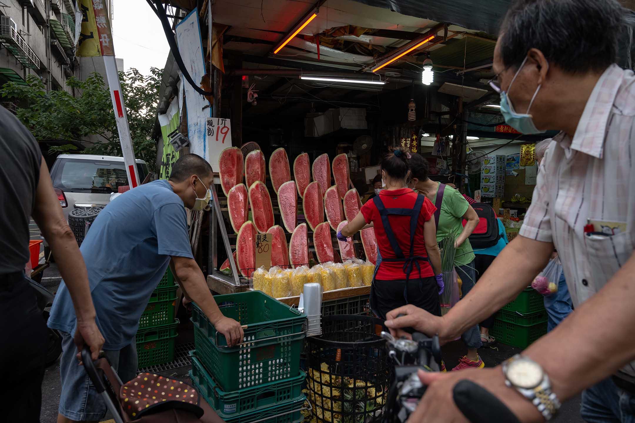 2021年5月27日台灣台北,戴著口罩的人們在市場上購買食物。