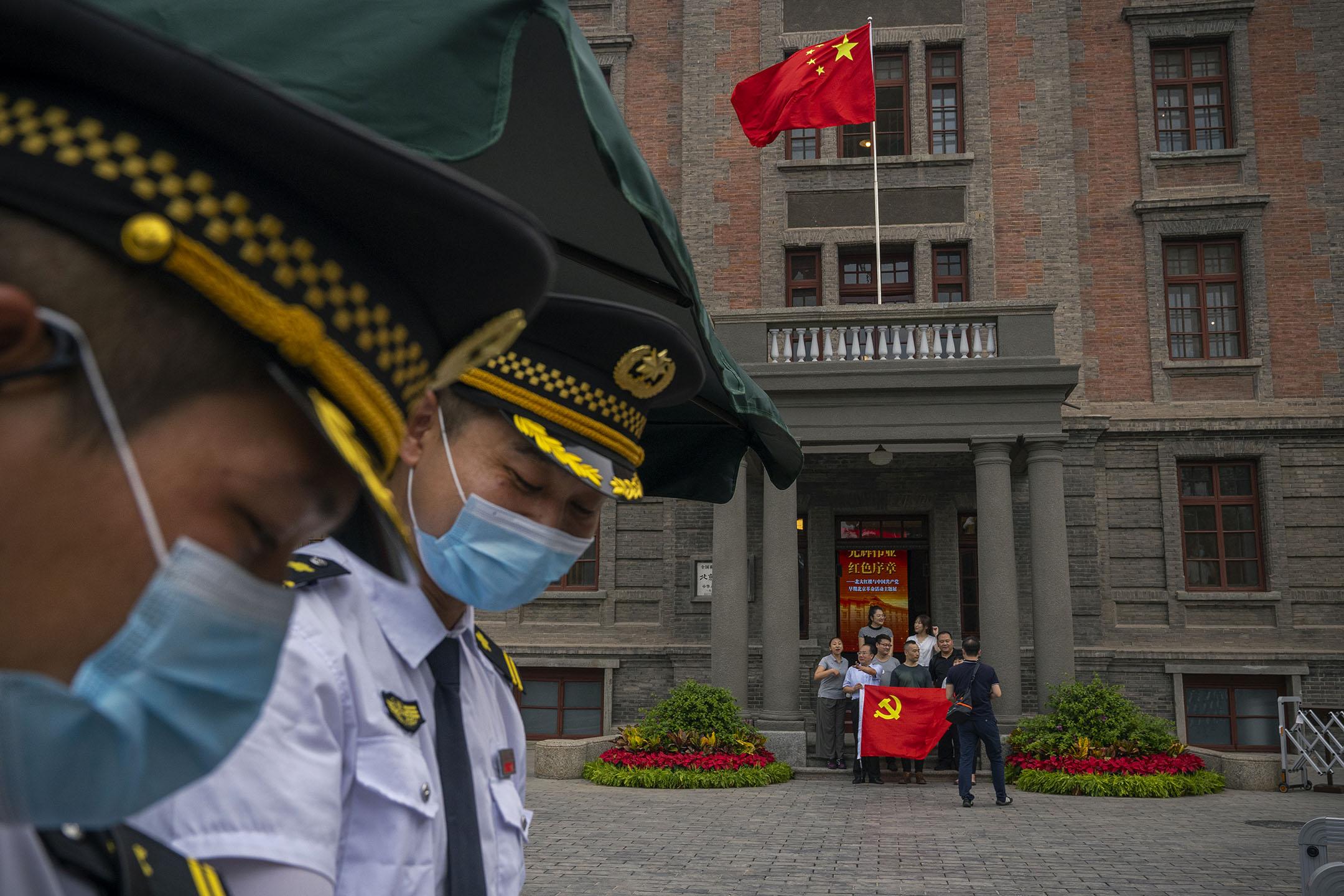 2021年6月30日,為慶祝共產黨成立100週年,人們拿著共產黨旗幟站在北京大學紅樓的門口拍照。