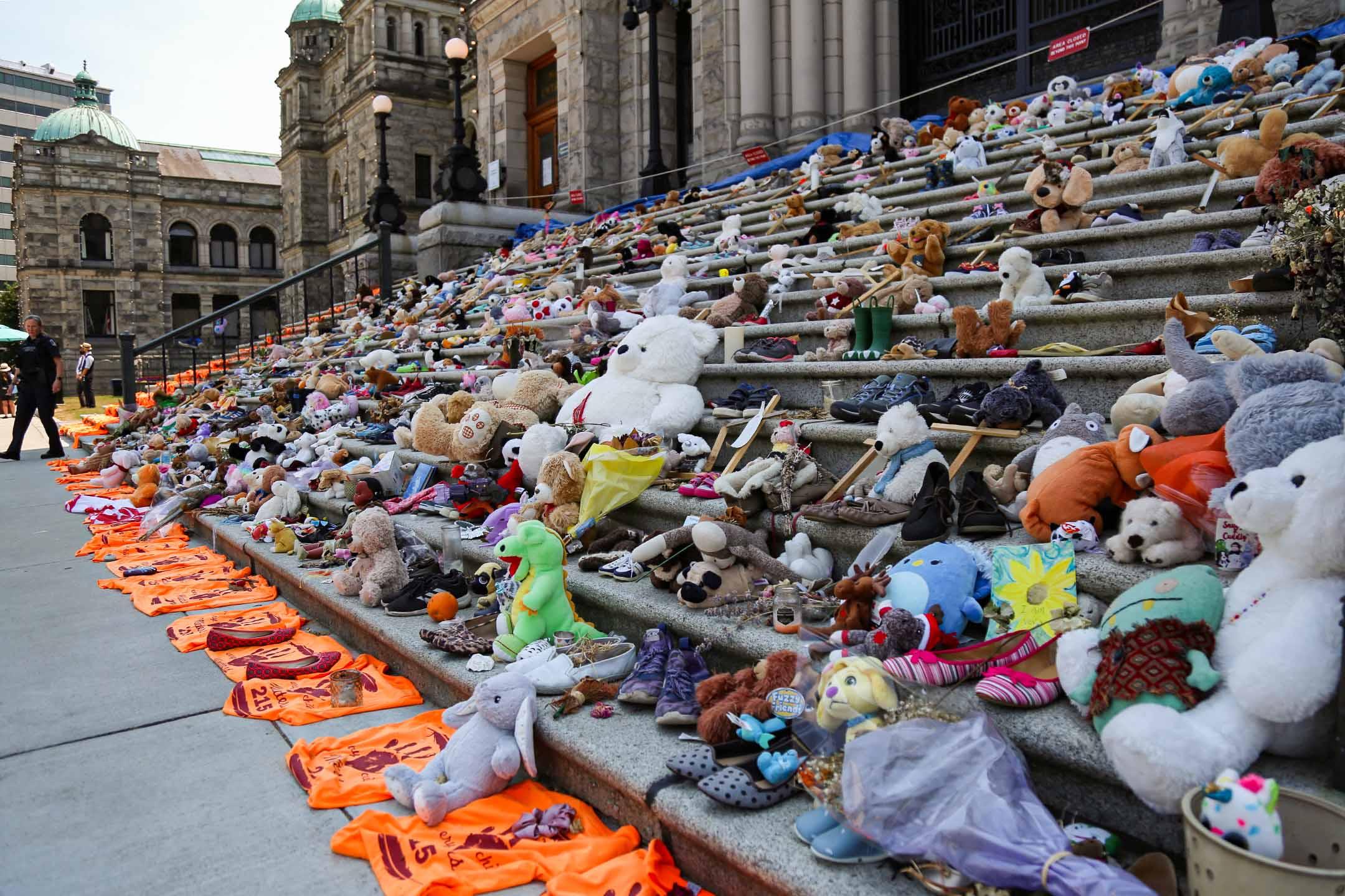 2021年6月30日加拿大不列顛哥倫比亞省議會大樓外,爲紀念埋在坎盧普斯寄宿學校的兒童而放置的玩具和鞋子。