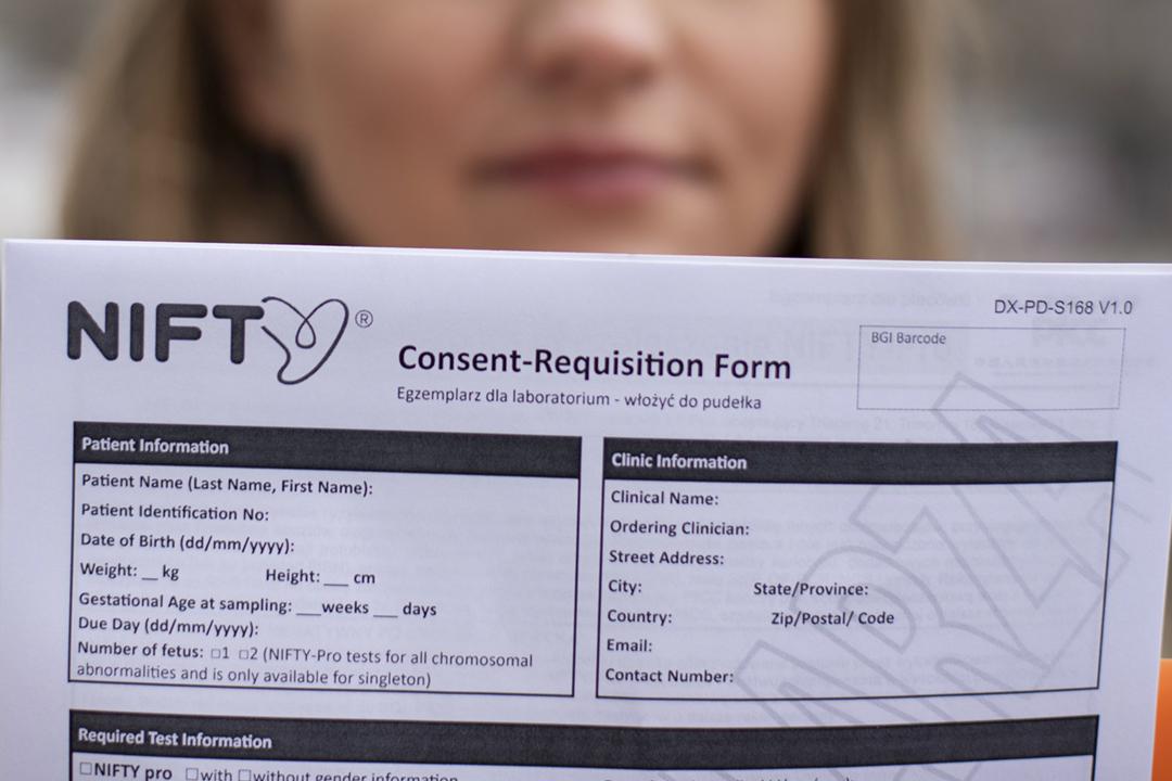 2021年3月30日在波蘭華沙,一名曾經接受華大基因 NIFTY 無創基因檢測的婦女,手持該項檢測的同意書讓記者拍攝。 攝:Kuba Stezycki / Reuters