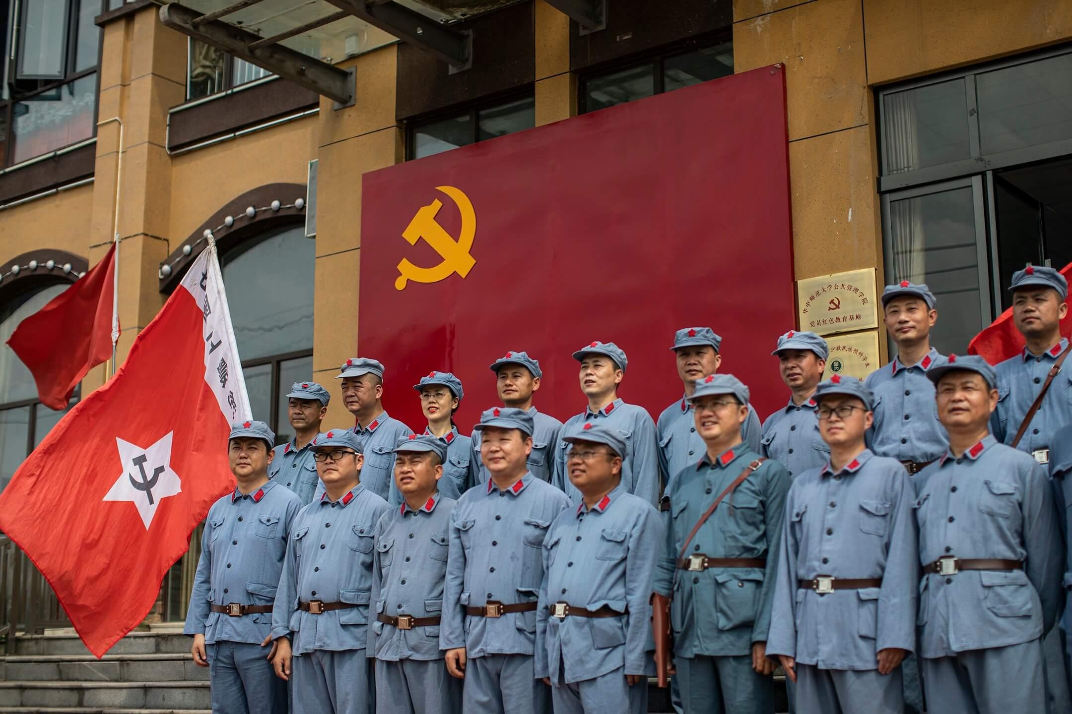 2021年6月26日,中國,穿上紅衛兵服裝的遊客到英山縣的長征精神體驗園參加活動,在中共黨旗下拍照留念。 攝:Stringer/Getty Images