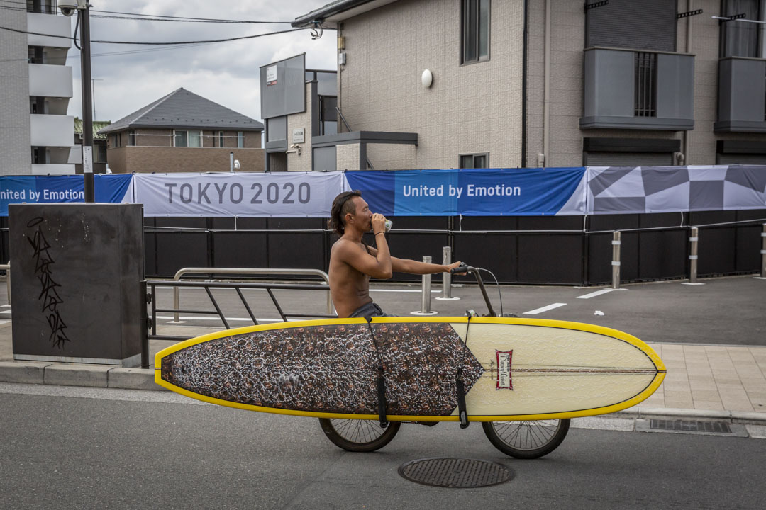 2021年6月28日日本藤澤市,一名衝浪者騎車經過東京奧運會的宣傳橫幅。