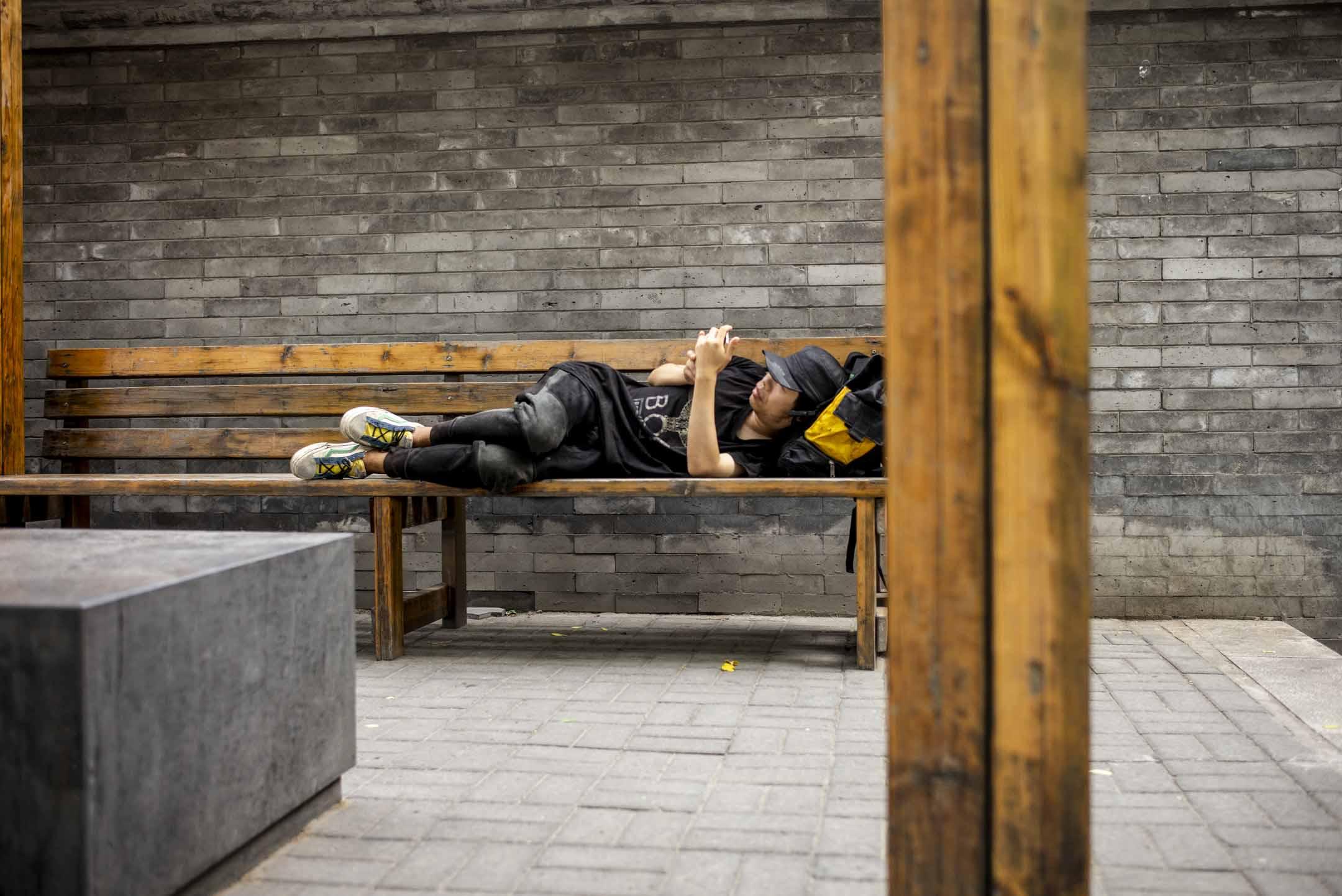 2021年6月2日,北京一個公園,青年在椅上躺著看手機。 攝:林振東/端傳媒