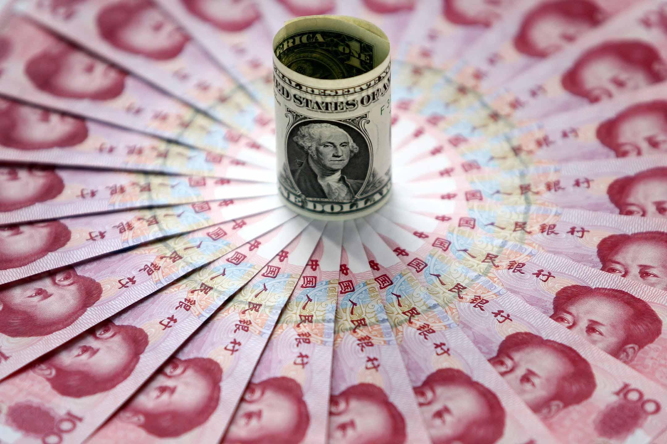 中國北京的一家銀行展示美元和 一百元人民幣。 攝:China Photos/Getty Images